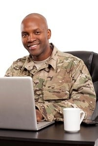 An American veteran soldier sitting at a laptop computer